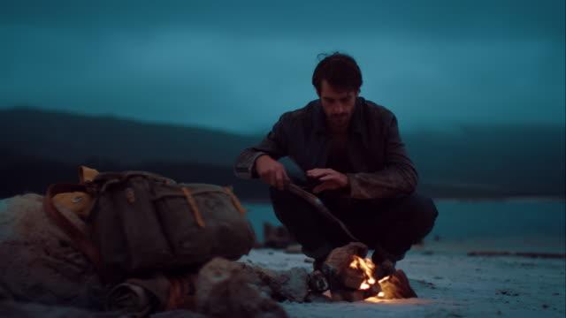 Man sitting at warm campfire