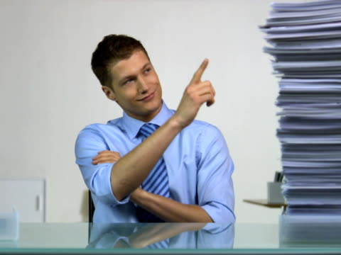 Man sitting behind a desk using his finger to decrease the pile of paper beside him Sweden.