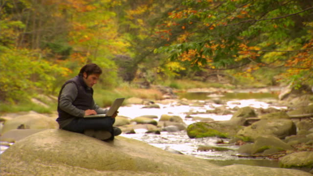 ws, man sitting by forest river and using laptop, autumn, phoenicia, new york, usa - アルスター郡点の映像素材/bロール