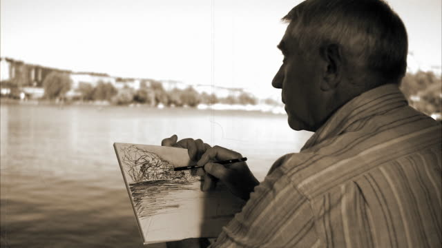 stockvideo's en b-roll-footage met a man sitting by the sea sketching stockholm sweden. - sepiakleurig