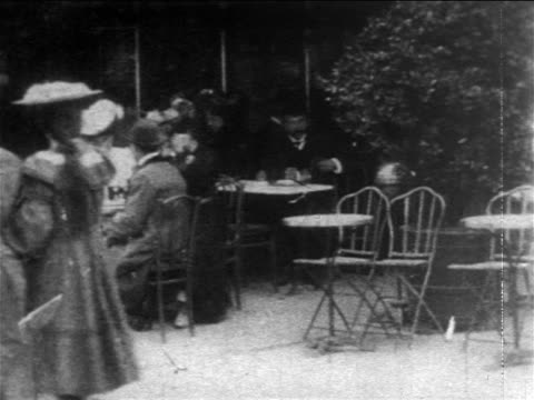 b/w 1904 pan man sitting down at sidewalk cafe + ordering pint of beer from waiter / france - paris france stock videos & royalty-free footage