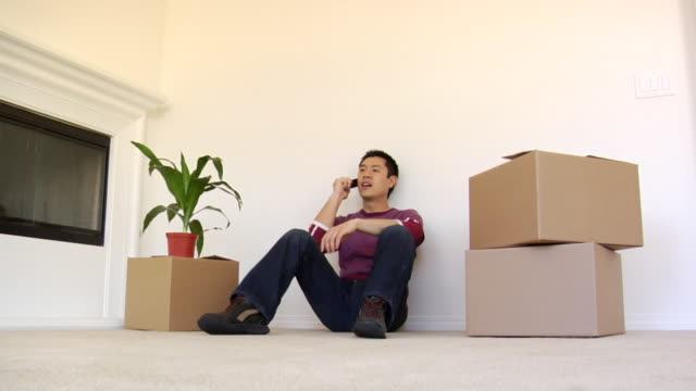 vídeos de stock e filmes b-roll de la ws man sitting down between moving boxes and talking on cell phone in new house / los angeles, california, usa - sentar se