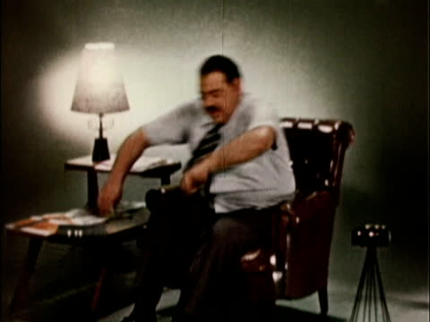 1956 ws td man sitting down in easy chair, kicking off shoes / usa - hemd und krawatte stock-videos und b-roll-filmmaterial