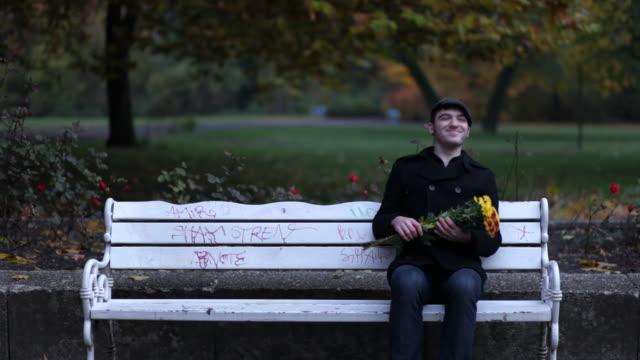 vídeos de stock, filmes e b-roll de homem sentando em banco de parque, uma reunião, duas fotos - sentando