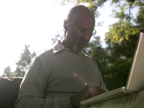 a man sitting in a park using a laptop sweden. - silver surfer stock videos & royalty-free footage
