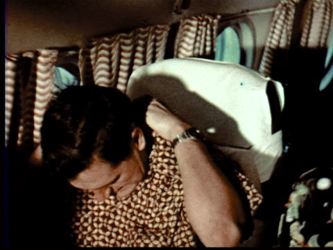 1957 MONTAGE Man sitting in airplane looks out window, smooth hair + straightens shirt collar. Male flight attendant helps passengers adjust seats. Woman puts on makeup as child reads magazine / Singapore / AUDIO