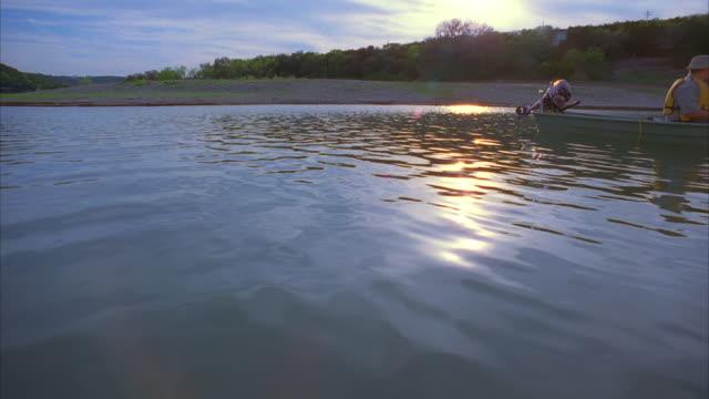 ws pan zi cs slo mo man sitting in boat and fishing / canyon lake, texas, usa - canyon lake stock videos & royalty-free footage