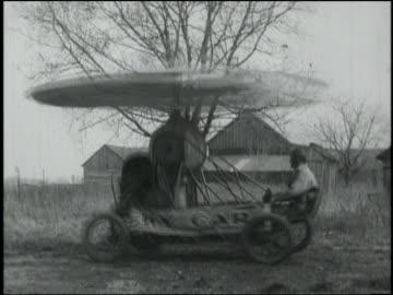 """vídeos y material grabado en eventos de stock de b/w man sitting in bouncing """"sky car"""" (early form of helicopter) - vehículo aéreo"""