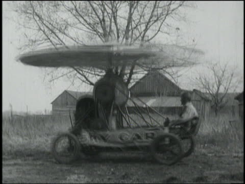 B/W man sitting in bouncing 'Sky Car' (early form of helicopter)
