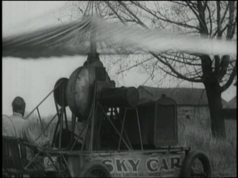"b/w man sitting in bouncing ""sky car"" (early form of helicopter) - air vehicle点の映像素材/bロール"