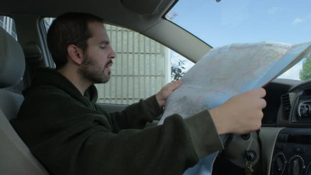 MS Man sitting in car and looking at road map / Campton, Kentucky, United States