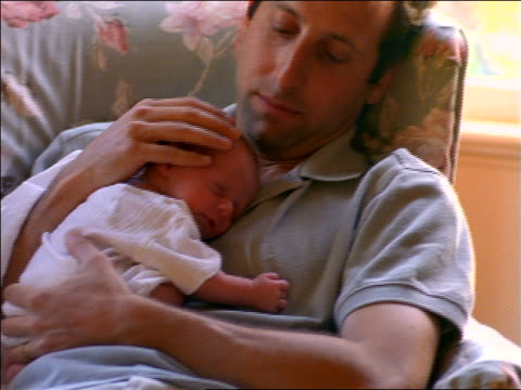 vidéos et rushes de man sitting in chair holding sleeping newborn baby girl - bébé de 0 à 6 mois