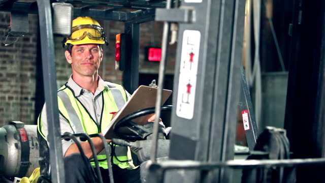 Man sitting in forklift looking at clipboard