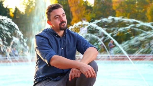 Man sitting in front of fountain waiting for a date
