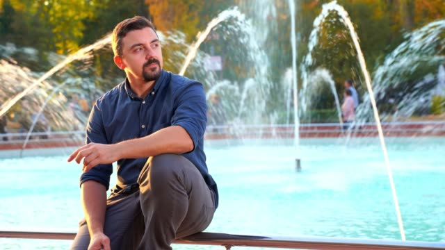 Man sitting in front of fountain waiting for a date which is late