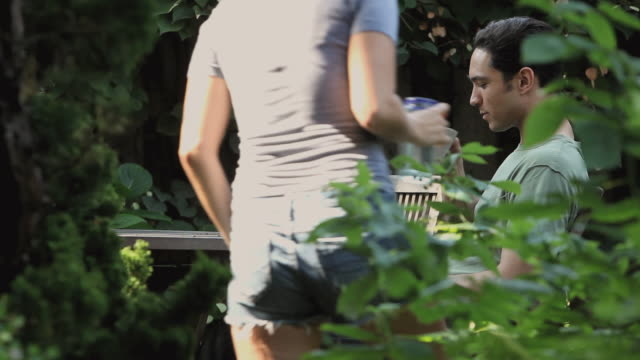 ms man sitting in garden, being joined by woman / jersey city, new jersey, usa - vegetable garden stock videos and b-roll footage
