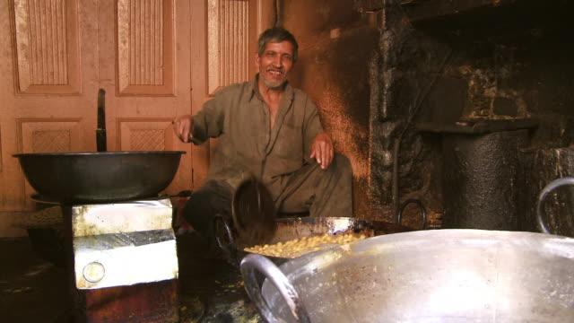 man sitting in kitchen smiling and stirring food  - お玉点の映像素材/bロール