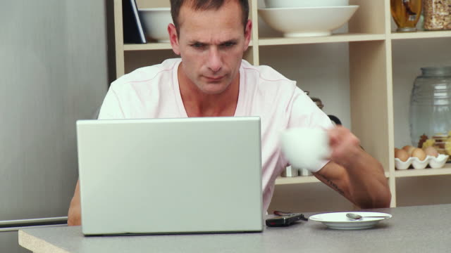 ms man sitting in kitchen, using laptop and drinking coffee / cape town, south africa - see other clips from this shoot 1811 stock videos & royalty-free footage