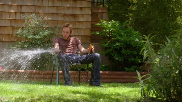 ws man sitting in lawn chair and watering grass with hose, then woman comes over and replaces his beer with hedge clippers / los angeles, california, usa - faulheit stock-videos und b-roll-filmmaterial