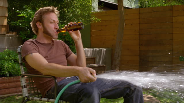 MS Man sitting in lawn chair and watering grass with hose, then woman comes over and replaces his beer with hedge clippers / Los Angeles, California, USA