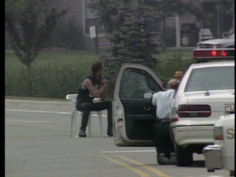 / man sitting in lawn chair in street intersection holding gun in his hand and point it to his head / man drinking soda / swat team lying on ground... - hands behind head stock videos & royalty-free footage