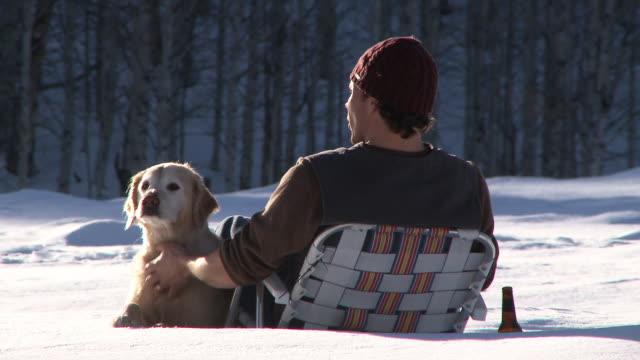 man sitting in lawn chair out in the snow with golden retriever and a beer / ketchum, idaho, united states - stroking stock videos & royalty-free footage