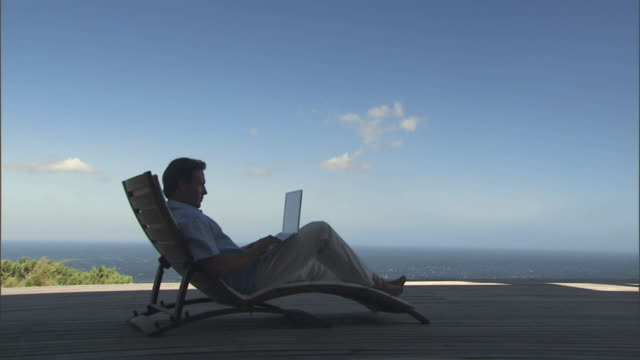 WS ZI Man sitting in lounge chair on deck overlooking the ocean and using laptop/ Cape Town, South Africa