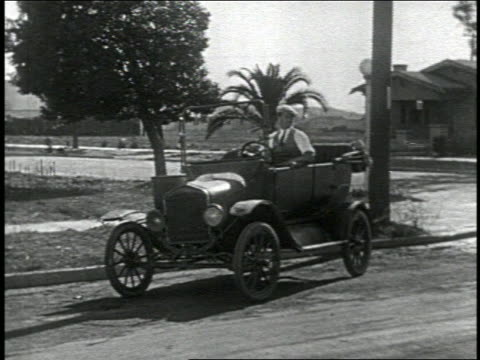 stockvideo's en b-roll-footage met b/w 1924 man sitting in parked convertible car on street / feature - 1924