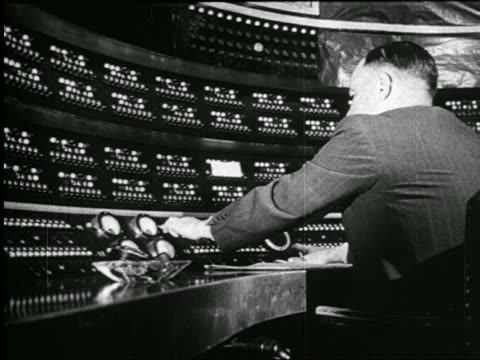 B/W 1938 REAR VIEW man sitting in radio studio operating control panel / newsreel