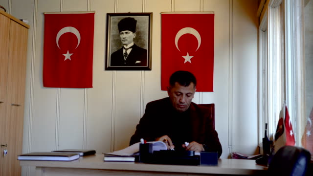 man sitting in small office with ata turk picture on wall behind - red tape stock videos & royalty-free footage