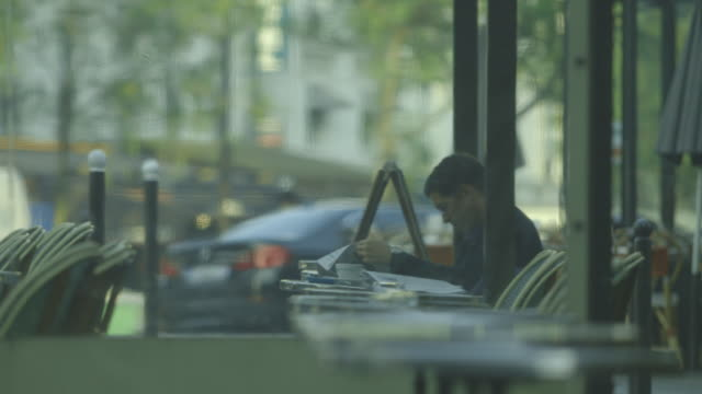 a man sitting in the covered area of a parisian brasserie is engrossed by a newspaper, france. - bbc news stock videos and b-roll footage