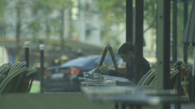 a man sitting in the covered area of a parisian brasserie is engrossed by a newspaper, france. - bbc news bildbanksvideor och videomaterial från bakom kulisserna