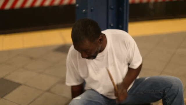 vídeos de stock e filmes b-roll de man sitting in the subwaystation playing drums - artista