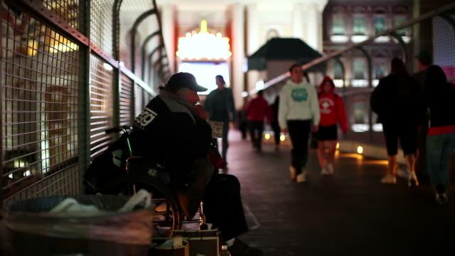 vidéos et rushes de ws  man sitting in wheelchair on city  walkway as people pass / las vegas,nevada,usa - las vegas