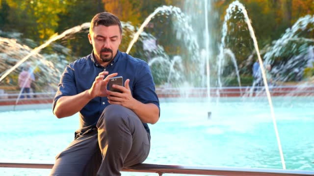 Man sitting near fountain using smart phone