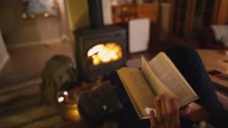 Man sitting near wood stove  in cozy cabin and reading book
