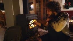 Man sitting near wood stove  in cozy cabin