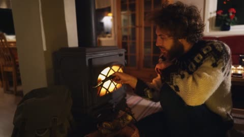man sitting near wood stove  in cozy cabin - wood material stock videos & royalty-free footage