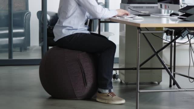 vidéos et rushes de homme s'asseyant sur une chaise de boule et travaillant sur l'ordinateur - sitting