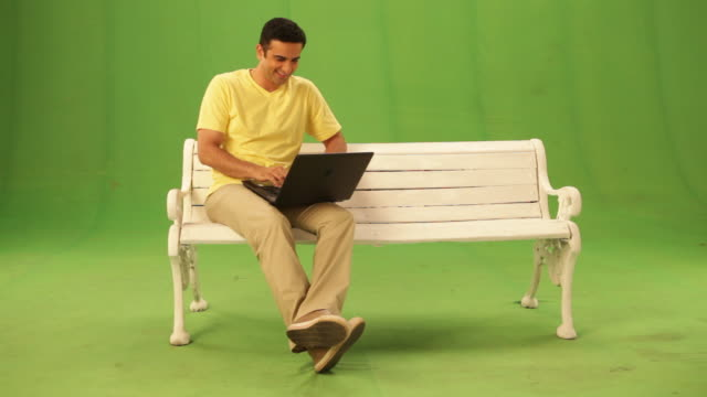 Man sitting on a bench and chatting on a laptop