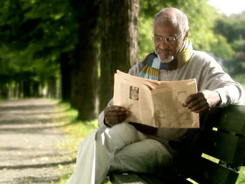 a man sitting on a bench reading a newspaper sweden. - old newspaper stock videos and b-roll footage