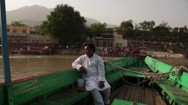 vídeos de stock, filmes e b-roll de man sitting on a boat at ganges river, laxman jhula, rishikesh, uttarakhand, india - rishikesh