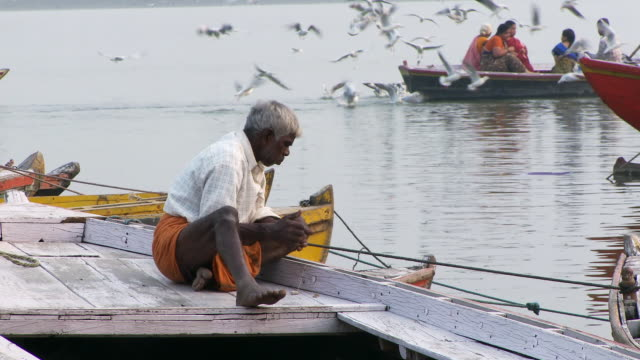 Man sitting on a boat working. India.