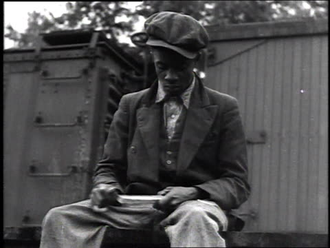 man sitting on a box onside a building / men reading newspaper / man lighting a cigarette / man whittling with a knife / men sitting heads in hands /... - bulletin board stock videos and b-roll footage