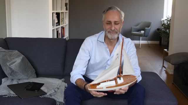 vídeos de stock e filmes b-roll de man sitting on a couch and viewing a sailing boat model - só homens maduros