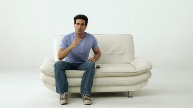 Man sitting on a couch and watching television