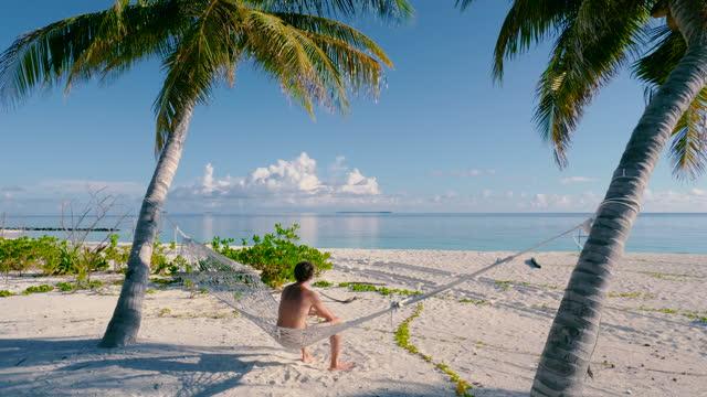 vídeos y material grabado en eventos de stock de hombre sentado en una hamaca entre dos palmeras en una playa - vestido parcialmente