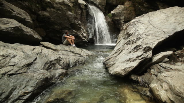 ws man sitting on a rock watching the waterfall / stowe, vermont, united states - stowe vermont stock videos & royalty-free footage