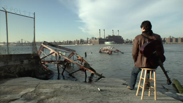 WS man sitting on a stool with guitar looking over collapsed pier toward smokstacks and Lower Manhattan from Brooklyn / New York City