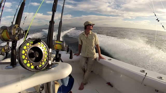 ms man sitting on back of sport fishing boat with flying rods and conventional tackle / iztapa, guatemala - one mid adult man only stock videos & royalty-free footage